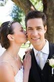 Beautiful bride kissing groom on cheek in garden Stock Image