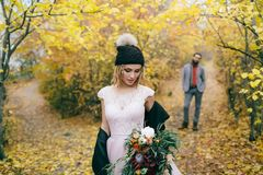 Beautiful bride in a knitted hat with a pompon are posing in autumn forest on blurred groom`s background. Wedding. Ceremony outdoors. Close-up portrait Royalty Free Stock Image