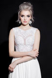 Beautiful bride in lace dress posing at camera, holding and touching her hands. Front view of blonde woman with stylish haircut, e Royalty Free Stock Image