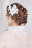 Beautiful bride with lace flowers in her gorgeous dark blond hair. High wedding hairstyle, braids and curls. Lace wedding dress Stock Photos