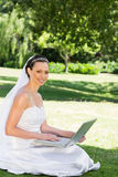 Beautiful bride with laptop sitting on grass Stock Images