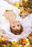 Beautiful bride liying down in the park. Royalty Free Stock Images