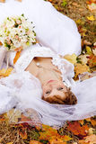 Beautiful bride liying down in the park. Stock Images