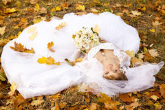 Beautiful bride liying down in the park. Stock Image