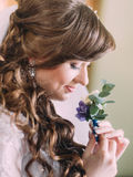 Beautiful bride with long curly hair and veil looking at the buttonhole indoors, close-up Royalty Free Stock Photo