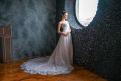 Beautiful bride in a long dress by the window stock photos