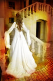 Beautiful bride in long silk coat on staircase. Beautiful bride with long brown hair in a long silk white coat with wide sleeves and feather trimming walking up Royalty Free Stock Photos