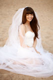 Beautiful bride with a long veil on the beach at sunset. Beautiful bride in a short dress with a long veil on the beach at sunset Royalty Free Stock Photography