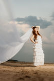 Beautiful bride with a long veil on the beach at sunset Stock Photo