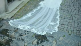 Beautiful Bride with Long Veil Down the Stairs of Stone