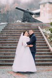 Beautiful bride in long white dress and elegant groom holding each other on stairs outdoors. Old cannon at background Stock Photos