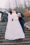 Beautiful bride in long white dress kissing with elegant groom on stairs outdoors. Old cannon at background Stock Photo