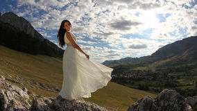 Beautiful bride in long white dress in nature. Panorama of young beautiful woman in long white dress with mountains in background Royalty Free Stock Photography