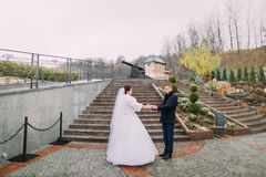 Beautiful bride in long white dress posing with elegant groom near stairs outdoors. Old cannon at background Stock Photography