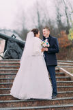 Beautiful bride in long white dress posing with elegant groom on stairs outdoors. Old cannon at background Royalty Free Stock Photos