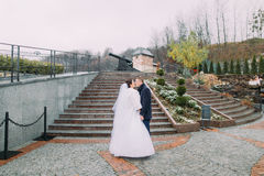 Beautiful bride in long white dress share kiss with elegant groom on stairs outdoors. Old cannon at background Stock Photography