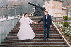 Beautiful bride in long white dress walking with elegant groom on stairs outdoors. Old cannon at background Stock Image