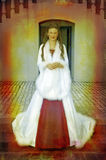 Beautiful bride in long white silk coat on staircase. Beautiful bride with long brown hair in a long silk white coat with wide sleeves and feather trimming and Royalty Free Stock Photos