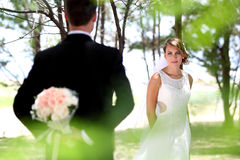 Beautiful bride looking at her groom. Hiding something Stock Photos