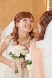 Beautiful bride  looking through mirror. And smiling Stock Image