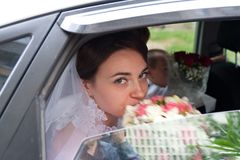 Beautiful bride looking out from car window Royalty Free Stock Photography