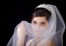 Beautiful Bride Looking Over Her Veil Against Blac. Beautiful bride looking over her veil as she hold it up in front of her face Stock Image