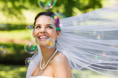 Beautiful bride looking at soap bubbles in park Stock Image