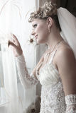 The beautiful bride looks out of the window Royalty Free Stock Photo
