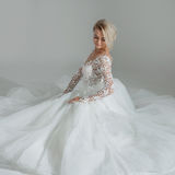 Beautiful bride in luxurious wedding dress, sitting in circle long skirts. White background, top view Stock Images