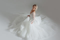 Beautiful bride in luxurious wedding dress, sitting in circle long skirts. White background, top view Stock Photography