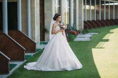 Beautiful bride in luxury fashion white wedding dress with veil on the green golf club glade, wedding day. Amazing full stock photos