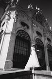 Beautiful bride in luxury wedding dress in front of palace.  royalty free stock image