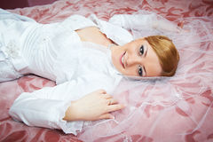 Beautiful bride lying on bed in wedding day stock images