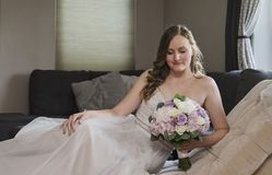 Beautiful bride lying on chaise lounge. Beautiful young bride sitting on couch with her bouquet in living room stock images