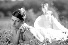 Beautiful bride lying in field. Beautiful bride in wedding dress lying in field Royalty Free Stock Photo