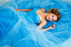 Beautiful bride lying on gorgeous blue dress Cinderella style royalty free stock photography