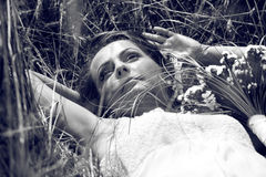 Beautiful bride lying on grass Royalty Free Stock Photography