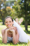 Beautiful bride lying on grass in park Royalty Free Stock Photography