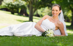 Beautiful bride lying on grass in park Stock Images