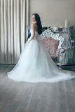Beautiful bride in a magnificent white wedding dress of tulle with a corset shooted back