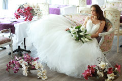Beautiful bride in a magnificent white wedding dress of tulle with a corset sitting on the sofa with bouquet lily and orchid. Beautiful bride in a magnificent Stock Photography