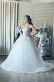 Beautiful bride in a magnificent white wedding dress of tulle with a corset. Beautiful young bride with long brown wavy hair in a lush white wedding dress of Stock Photos