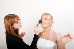 Beautiful bride and make-up artist Stock Photography