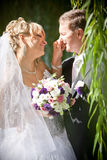 Beautiful bride making fun with groom and touching his nose Stock Image