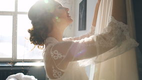 Beautiful bride in the morning of wedding day touching her dress and smiling stock video footage