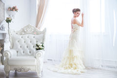 Beautiful bride near curtains with a bouquet. The bride sits on a antique chair with a bouquet in a wedding dress indoor Stock Image
