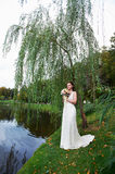 Beautiful bride near lake in autumn park Royalty Free Stock Photos