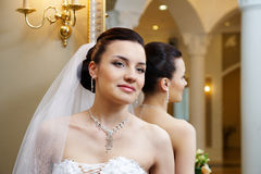 Beautiful bride near mirror in wedding palace Royalty Free Stock Image