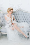 A beautiful bride in a negligee is sitting on the sofa eligantly. Beautiful bride in a peignoir in a bright room sits elegantly on a sofa Stock Image