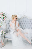 A beautiful bride in a negligee is sitting on the sofa eligantly. Beautiful bride in a peignoir in a bright room sits elegantly on a sofa surrounded by flowers stock photo
